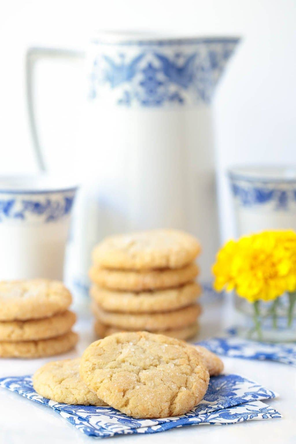 Photo of piles of Lemon Coconut Sugar Cookies in front of a white and delft blue milk pitcher and cups.