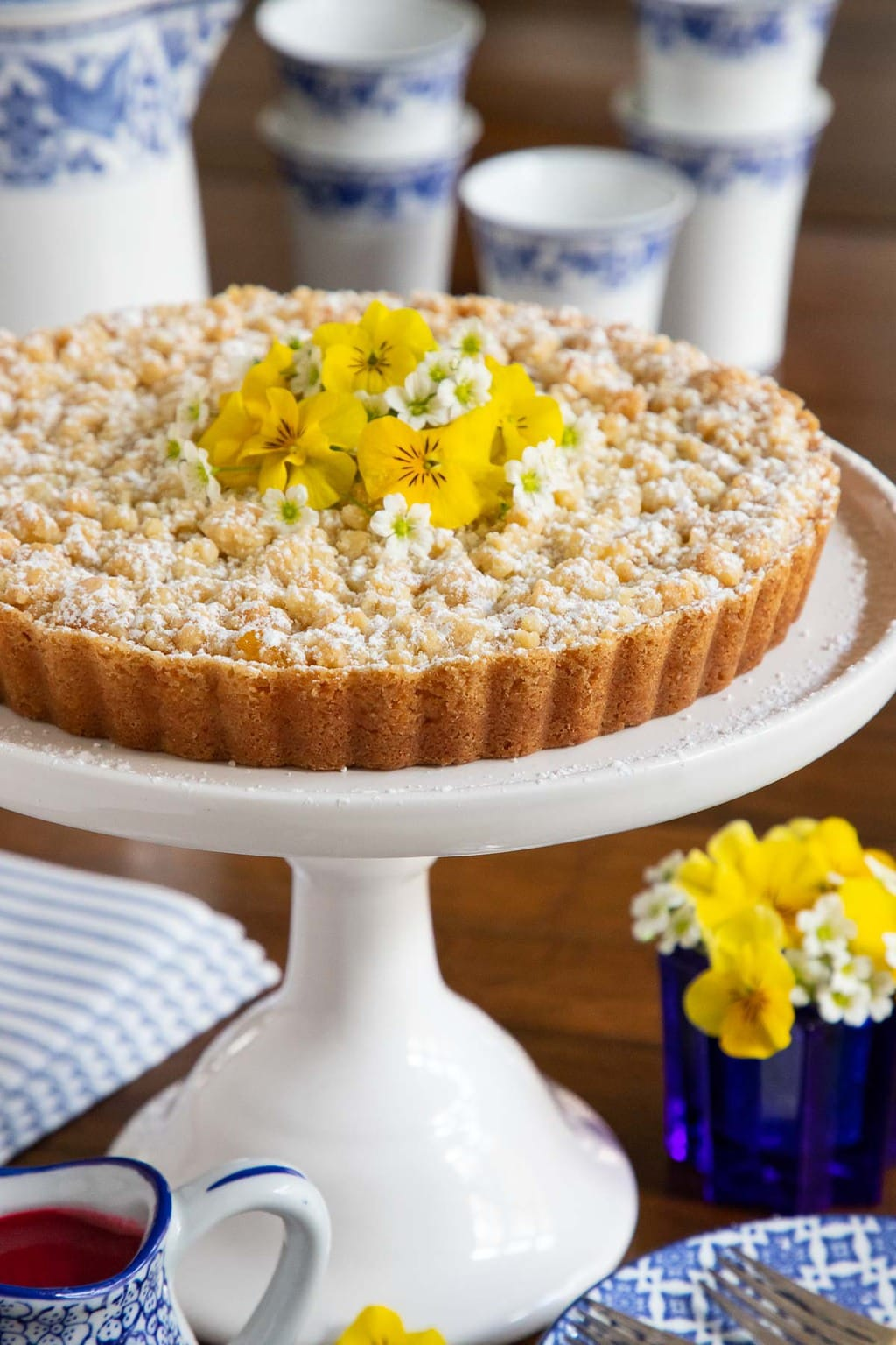 Vertical closeup photo of Lemon Curd Shortbread Tart on a white pedestal cake stand with yellow flowers.