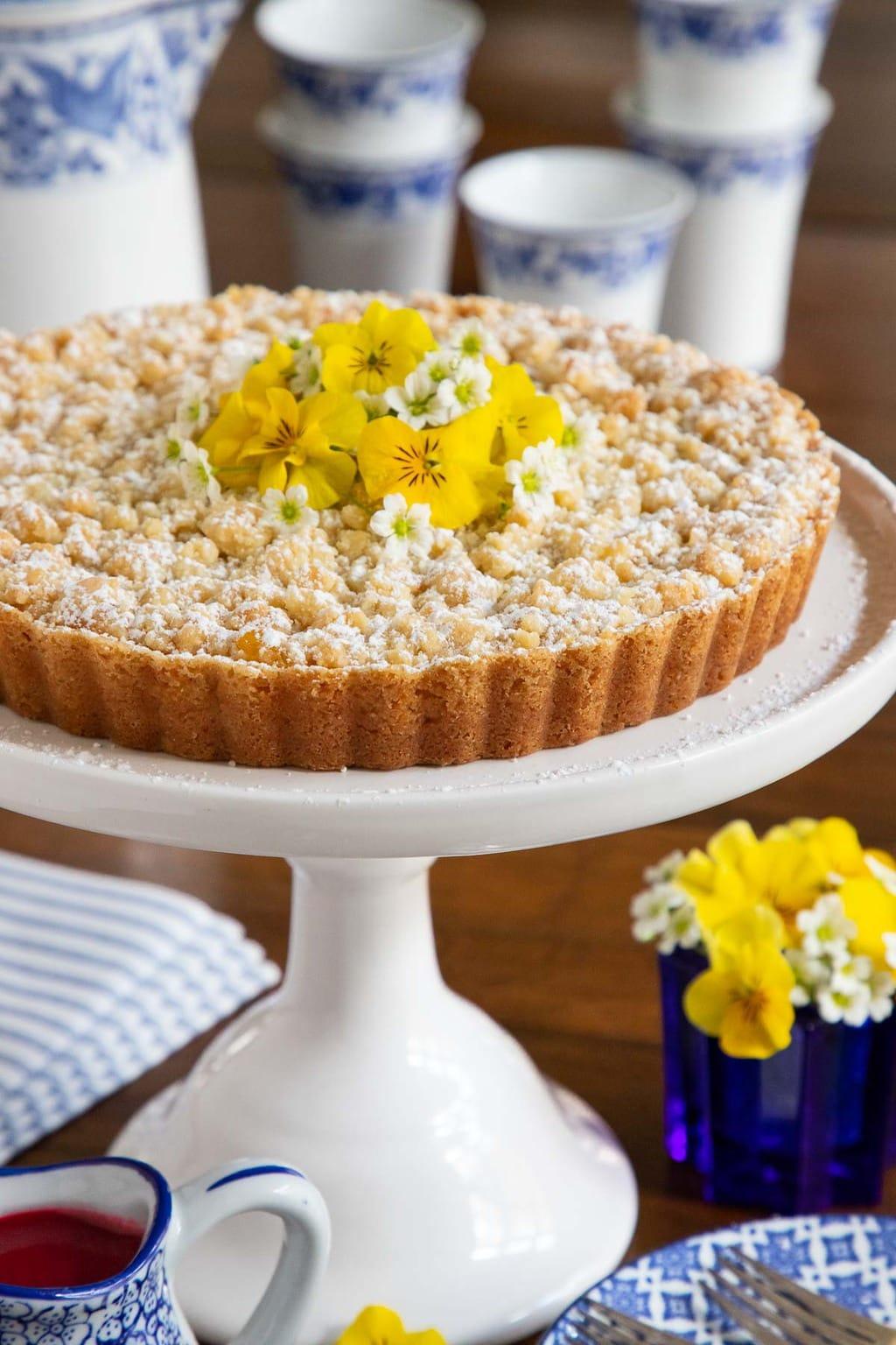 Photo of a Lemon Curd Shortbread Tart on a white cake pedestal platter.