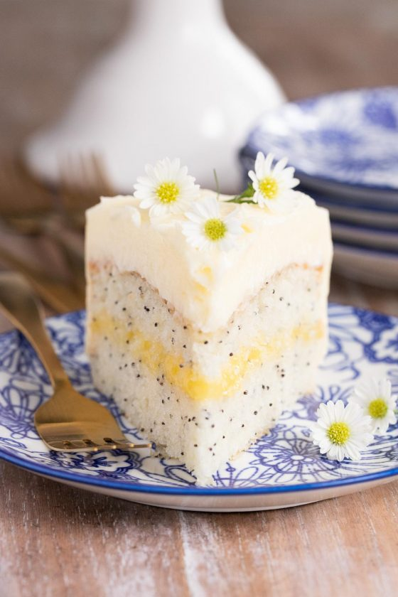 Vertical photo of a slice of Lemon Curd Poppy Seed Cake on a blue and white serving plate.