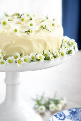 Vertical picture of lemon curd poppy seed cake decorated with flowers on a white cake stand.