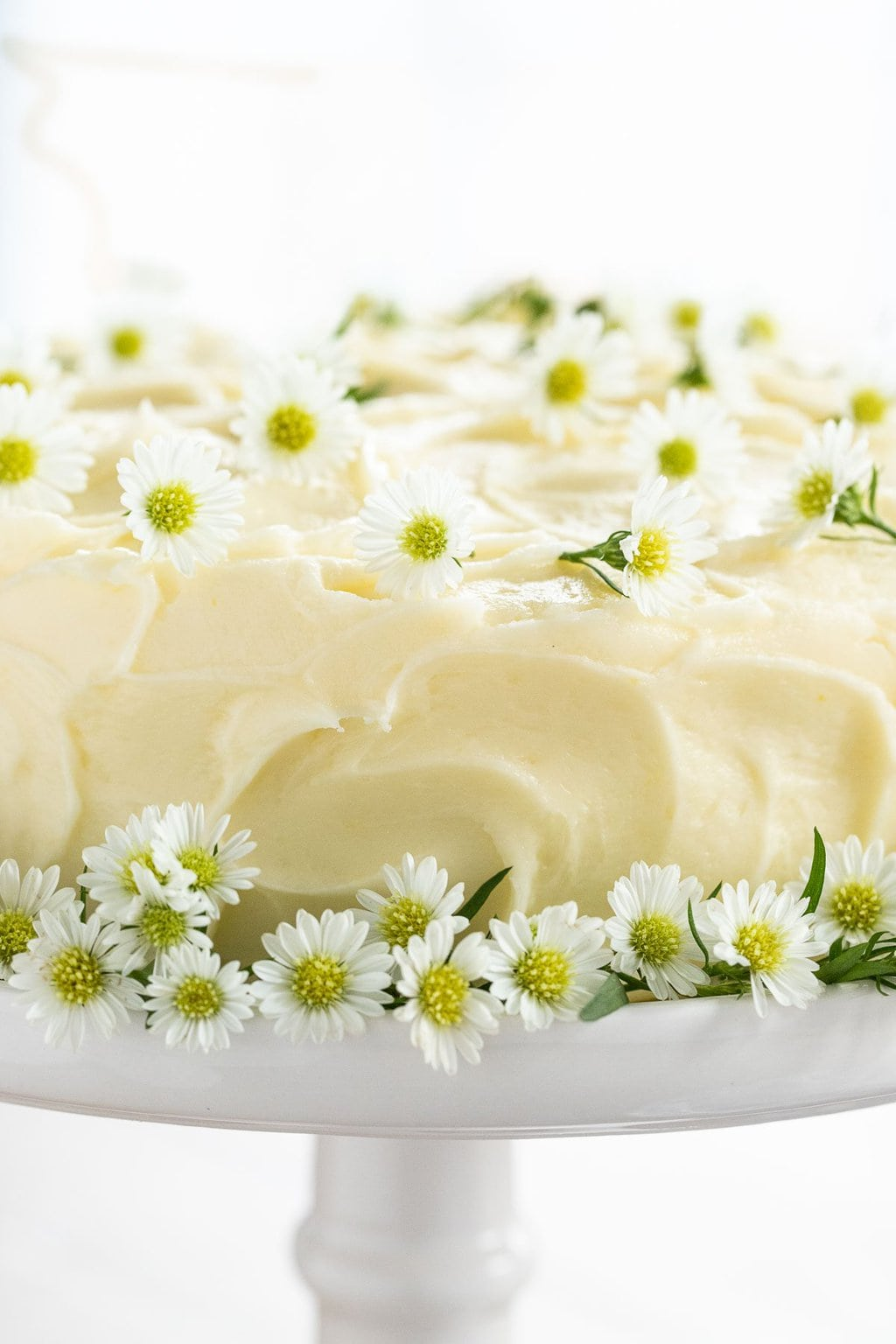 Ultra closeup of a Lemon Curd Poppy Seed Cake decorated with edible spring flowers.