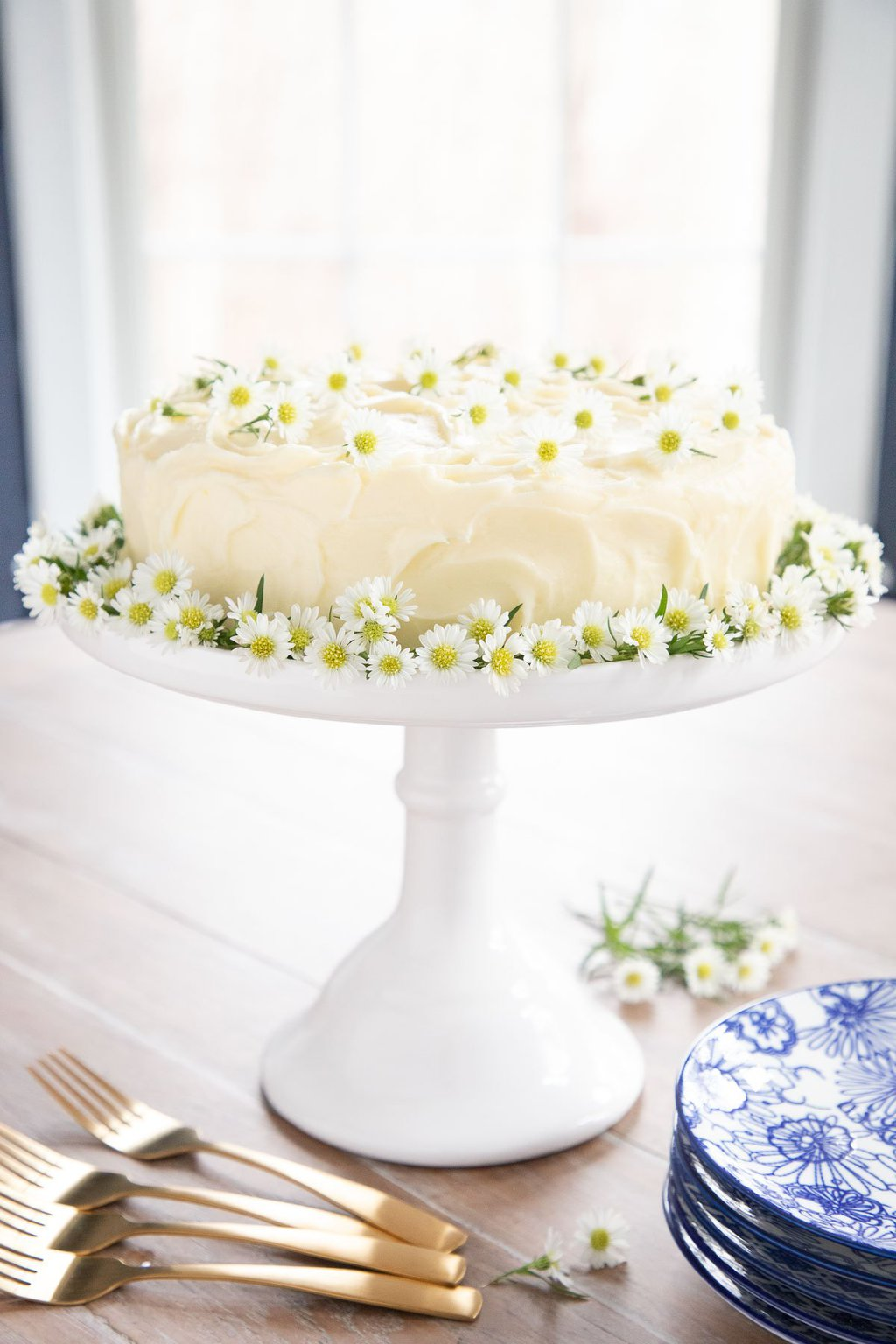 Over all photo of a Lemon Curd Poppy Seed Cake on a white pedestal cake stand decorated with edible flowers.
