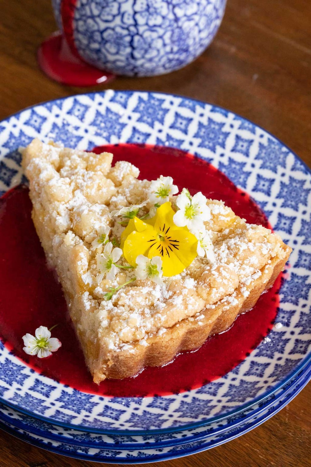 Photo of a slice of Lemon Curd Shortbread Tart in a pool of raspberry coulis decorated with yellow pansies.
