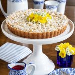 Vertical picture of Lemon Curd Shortbread Tart on a white cake stand
