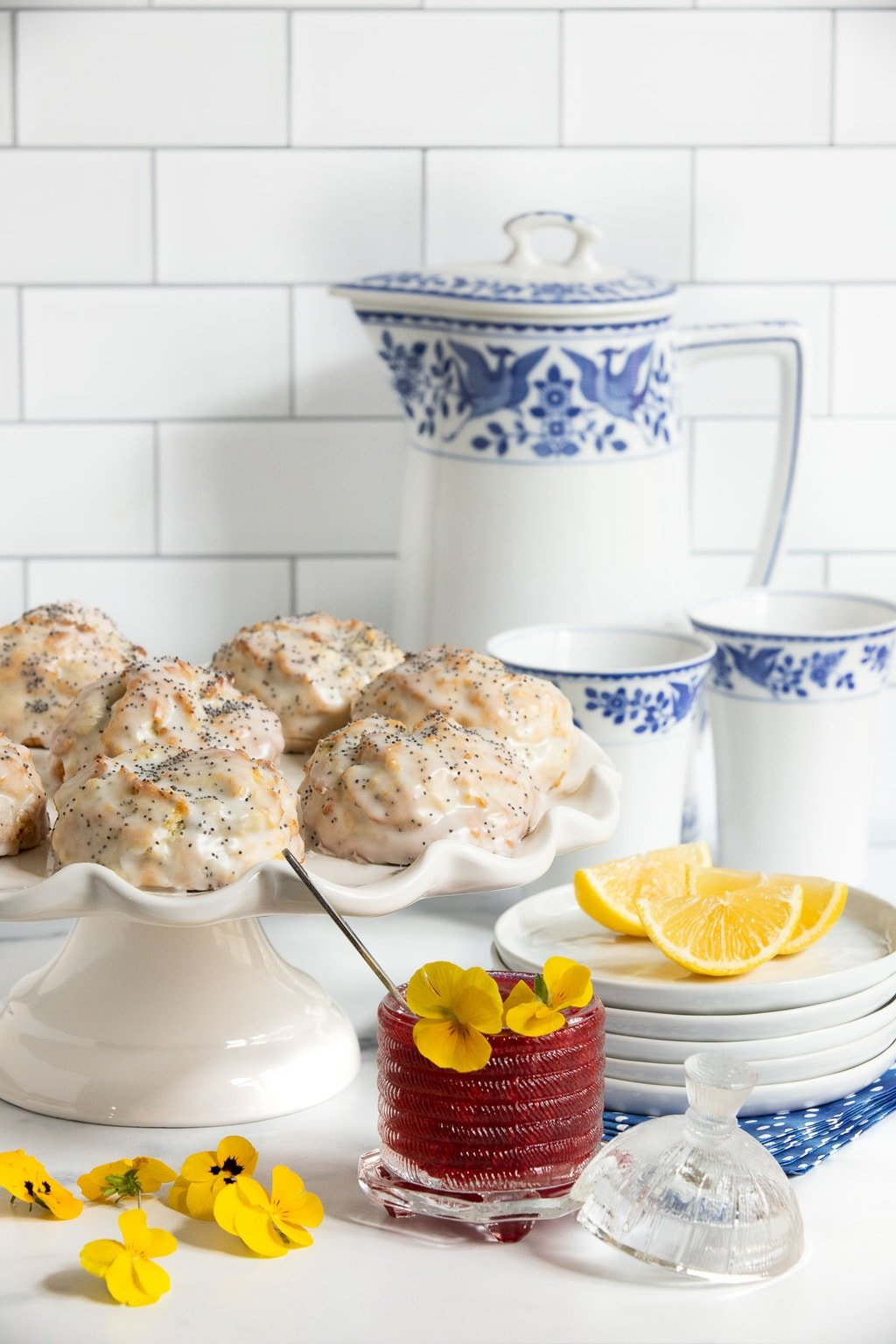 Vertical photo of a batch of Ridiculously Easy Lemon Poppy Seed Scones on a white scalloped pedestal serving plate with a small jar of Raspberry Freezer jam in the foreground with yellow pansies.