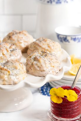 Vertical photo of a batch of Lemon Poppy Seed Scones on a white pedestal serving platter with a small jar of Raspberry Freezer Jam in the foreground.