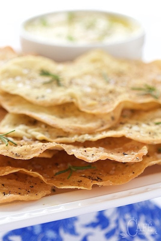 Photo of a serving plate of Lemon Rosemary Flatbread Crackers with a bowl of appetizer dip in the background.