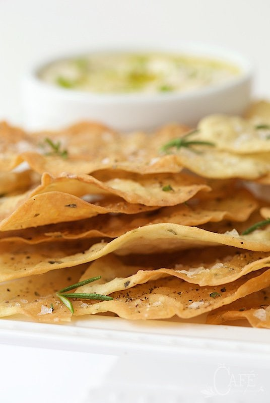 Closeup photo of a white appetizer tray of Lemon Rosemary Flatbread Crackers with a bowl of appetizer dip in the background.