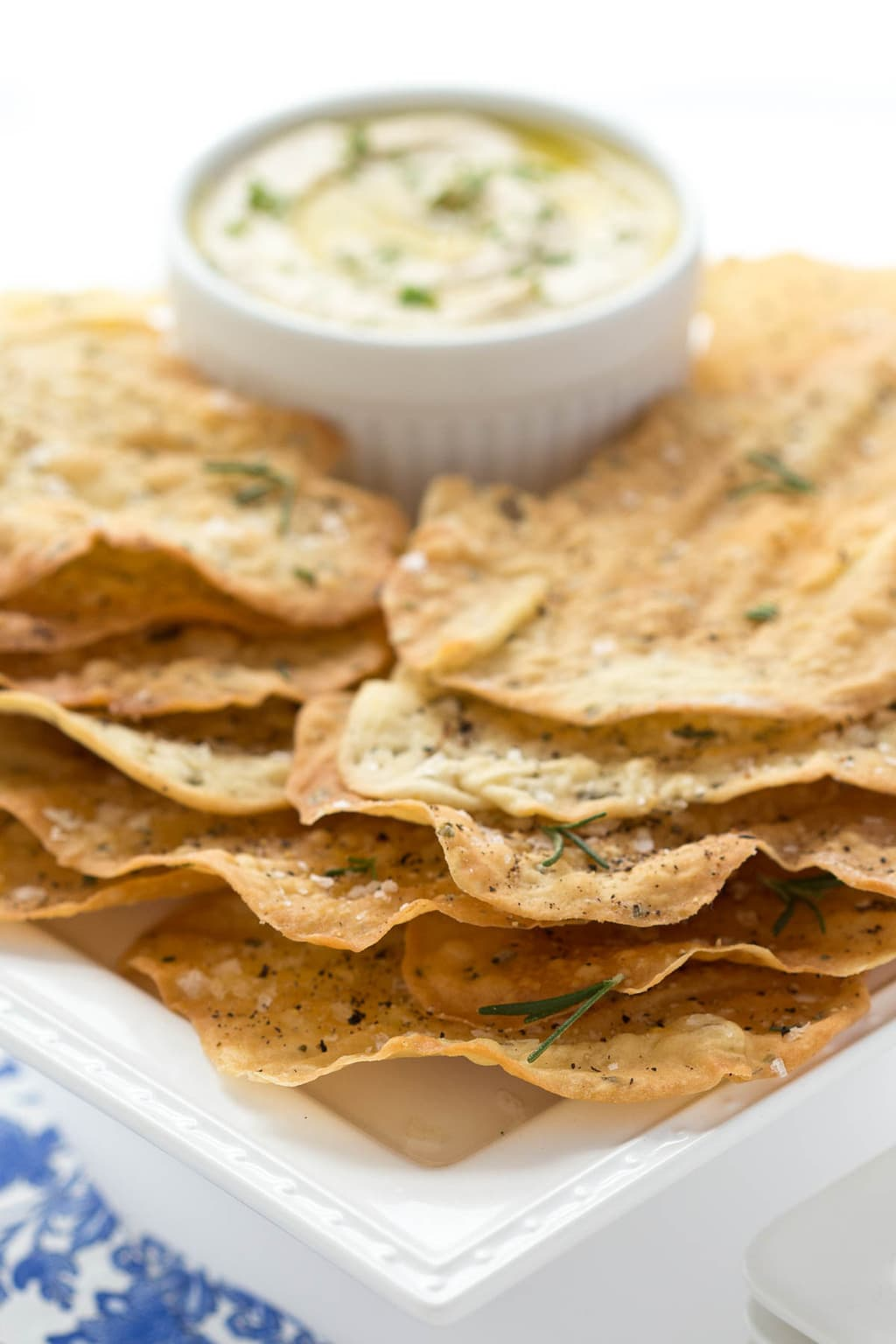 Vertical photo of Lemon Rosemary Flatbread Crackers on a white platter with dip in the background.