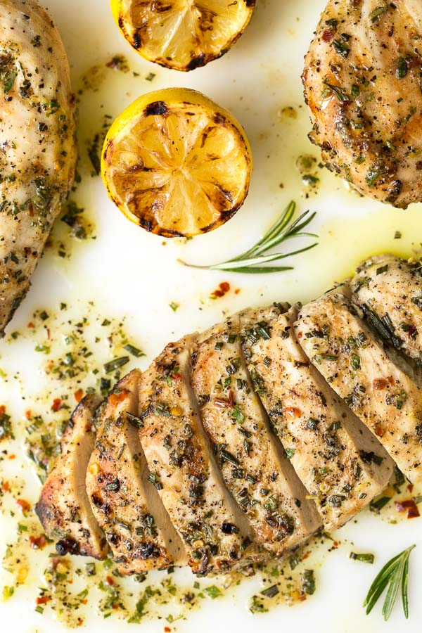 Overhead photo of Lemon Rosemary Grilled Chicken Breasts rubbed with lemon-rosemary-garlic rub and garnished with grilled lemons and rosemary sprigs.
