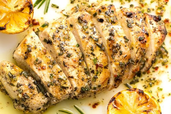 Overhead closeup photo of Lemon Rosemary Grilled Chicken Breasts garnished with grilled lemons and rosemary sprigs.
