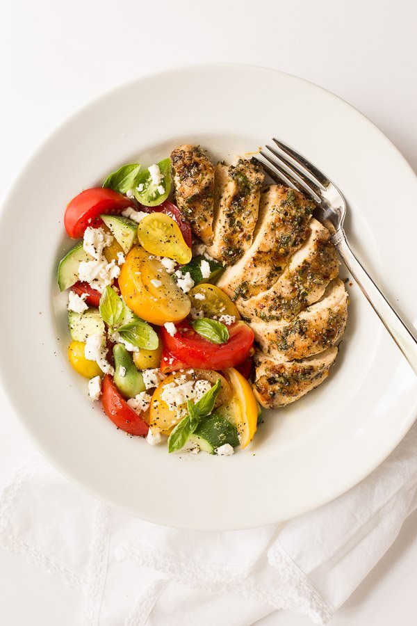 Overhead photo of a plate of Lemon Rosemary Grilled Chicken Breasts on a white surface.