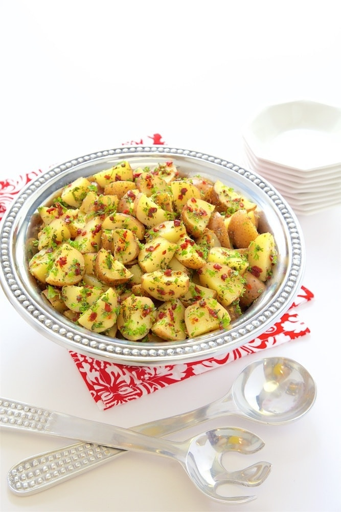 Vertical picture of Lemon, Rosemary and Sundried Tomato Potato Salad in a silver bowl on a red and white napkin