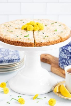 Vertical closeup photo of Lemon Thyme Shortbread on a white pedestal stand surrounded by yellow daisies.
