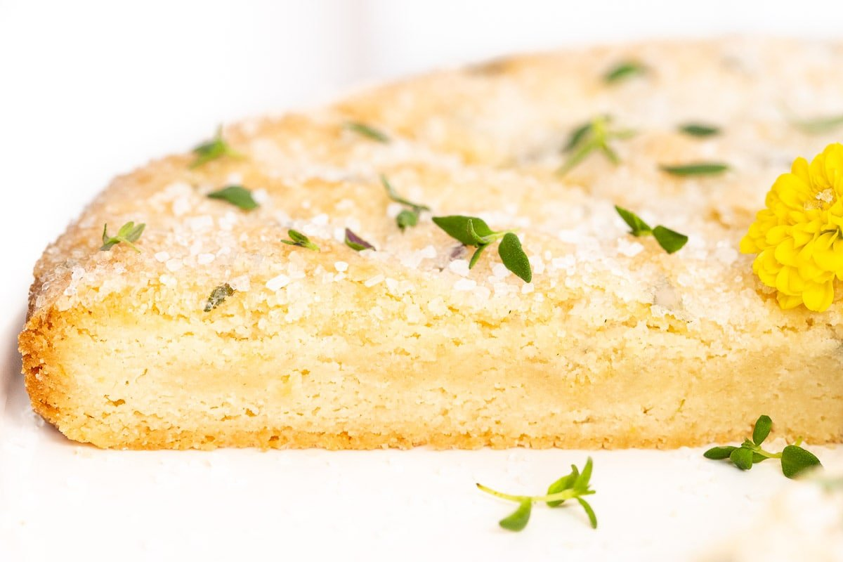 Horizontal extreme closeup photo of the inside and top of Lemon Thyme Shortbread garnished with fresh thyme and yellow daisies.