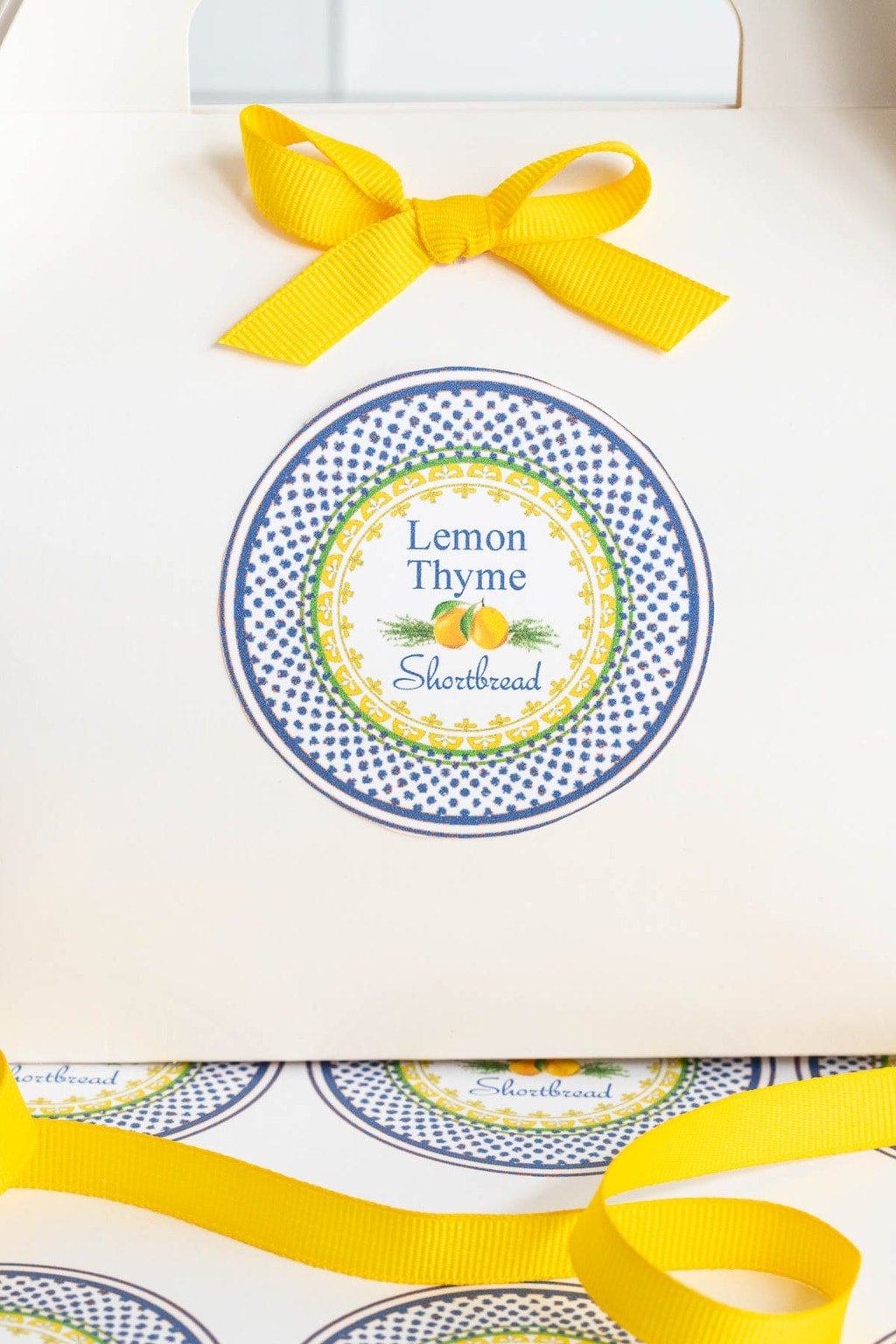 Vertical photo of a white gift box for gifting Lemon Thyme Shortbread including a custom label.