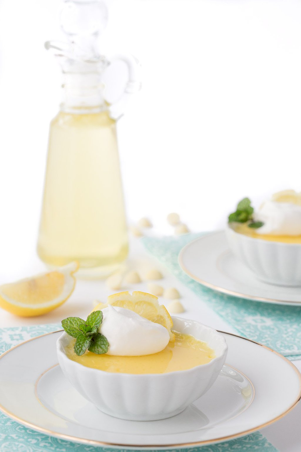Photo of small white bowls of Lemon and White Chocolate Pots de Crème garnished with mint leaves and whipped cream with Limoncello Syrup in a small glass pitcher in the background.
