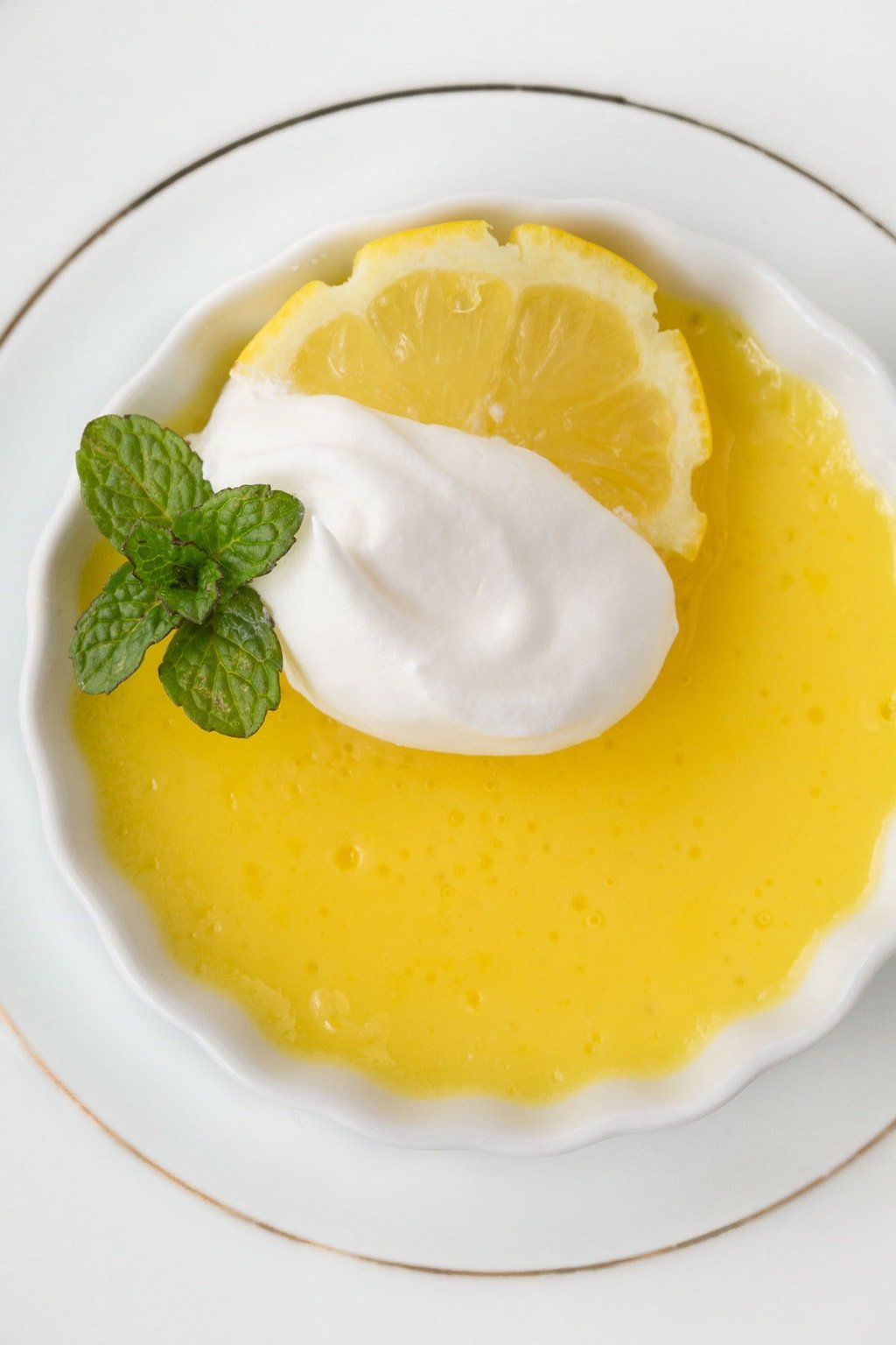 Overhead photo of a white dish of Lemon and White Chocolate Pots de Crème garnished with mint, a lemon slice and whipped cream.