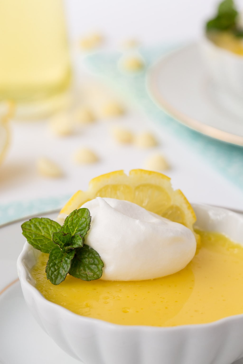 Closeup photo of a fluted white bowl of Lemon and White Chocolate Pots de Crème garnished with a lemon, mint and whipped cream with a small pitcher of Limoncello Syrup and white chocolate chips in the background.
