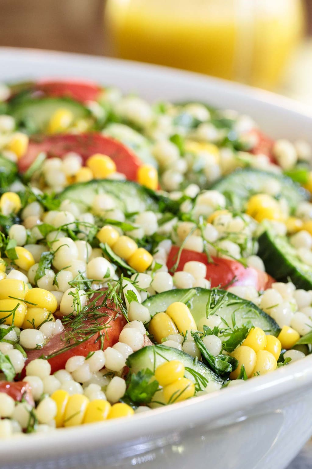 Ultra closeup photo of a Mediterranean Couscous Salad in a white serving bowl.