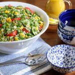 Vertical picture of lemony couscous salad in a white bowl on a wooden table with small blue and white bowls stacked