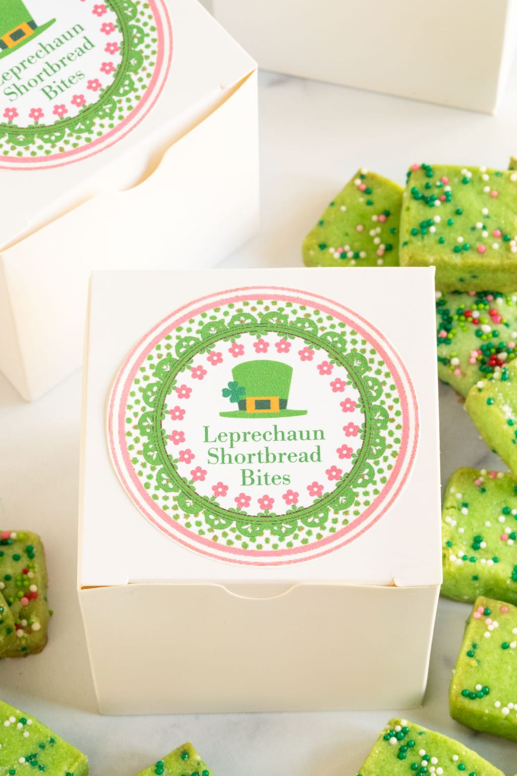 Extreme closeup vertical photo of Leprechaun Shortbread Bites in a small white gift box with a custom gift label attached.