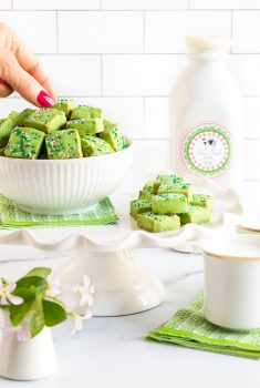 Vertical photo of a bowl of Leprechaun Shortbread Bites on a pedestal display stand with a shamrock plant in the foreground and a quart of Irish milk in the background. A hand is taking one of the shortbread bites.