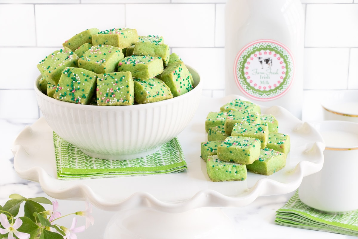Horizontal photo of Leprechaun Shortbread Bites in a white bowl and stacked on a pedestal display stand. A quart of Irish milk is in the background with a shamrock plant in the foreground.