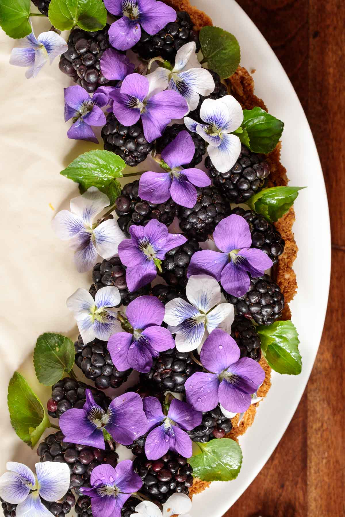 Overhead photo of a Limoncello Lemon Tart decorated with wild violet flowers, leaves and blackberries.