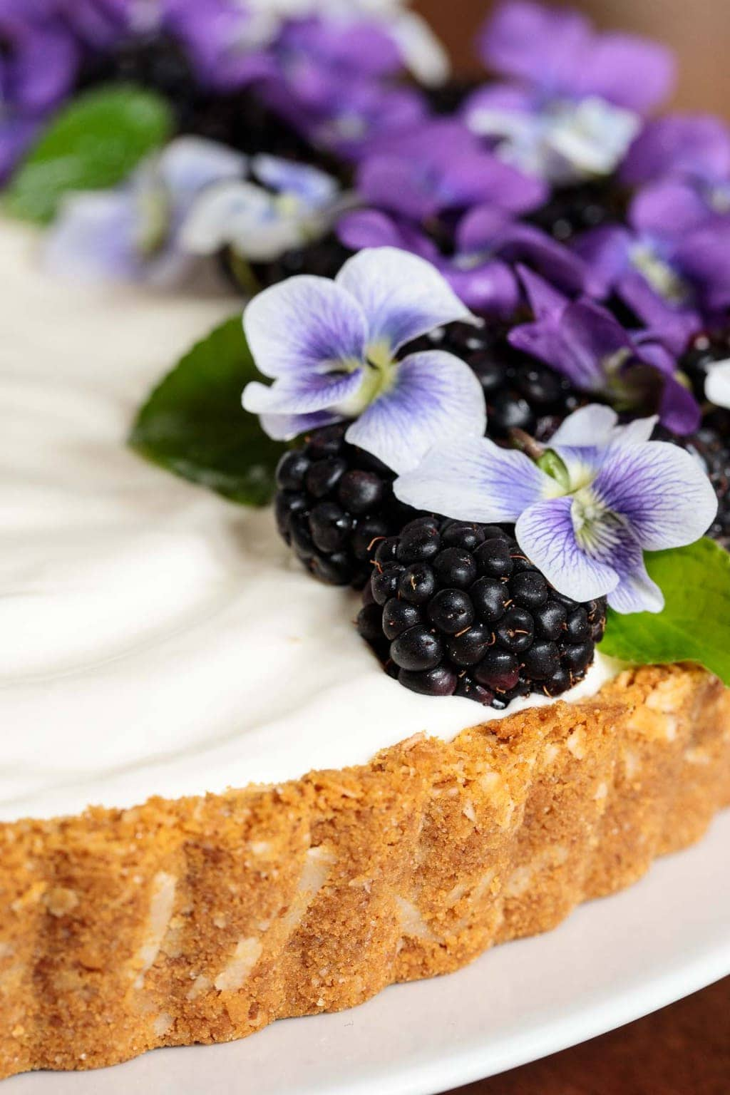 Closeup photo of a Limoncello Lemon Tart decorated with edible wild violets, leaves and fresh blackberries.