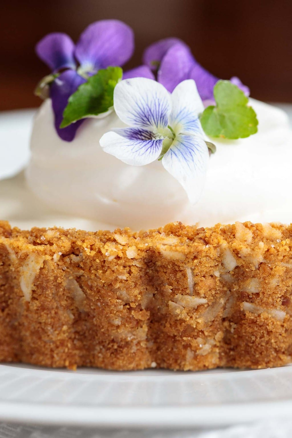 Extreme closeup of the crust of a Limoncello Lemon Tart decorated with whipped cream and wild violets.