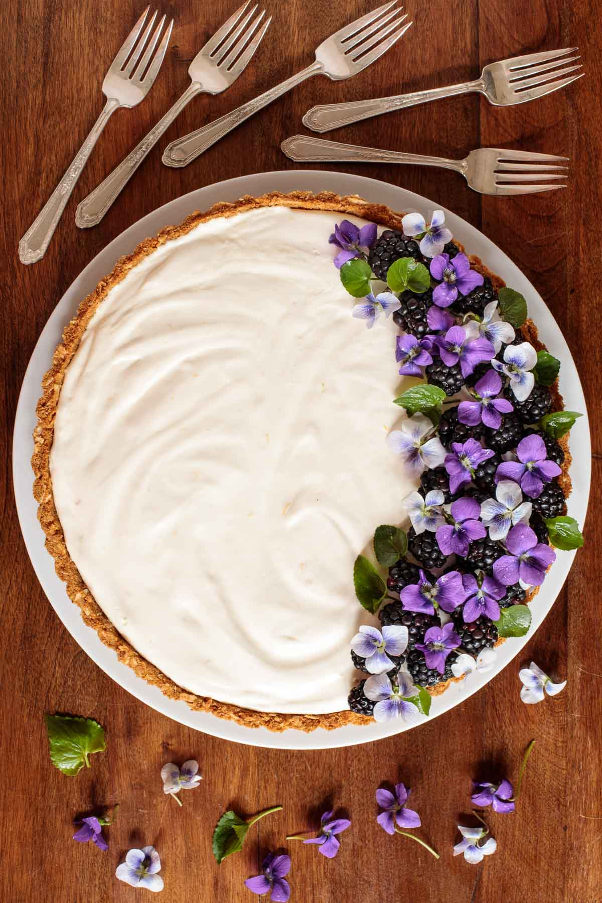 Overhead photo of a Limoncello Lemon Tart on a wood table surrounded by serving forks and wild violets.