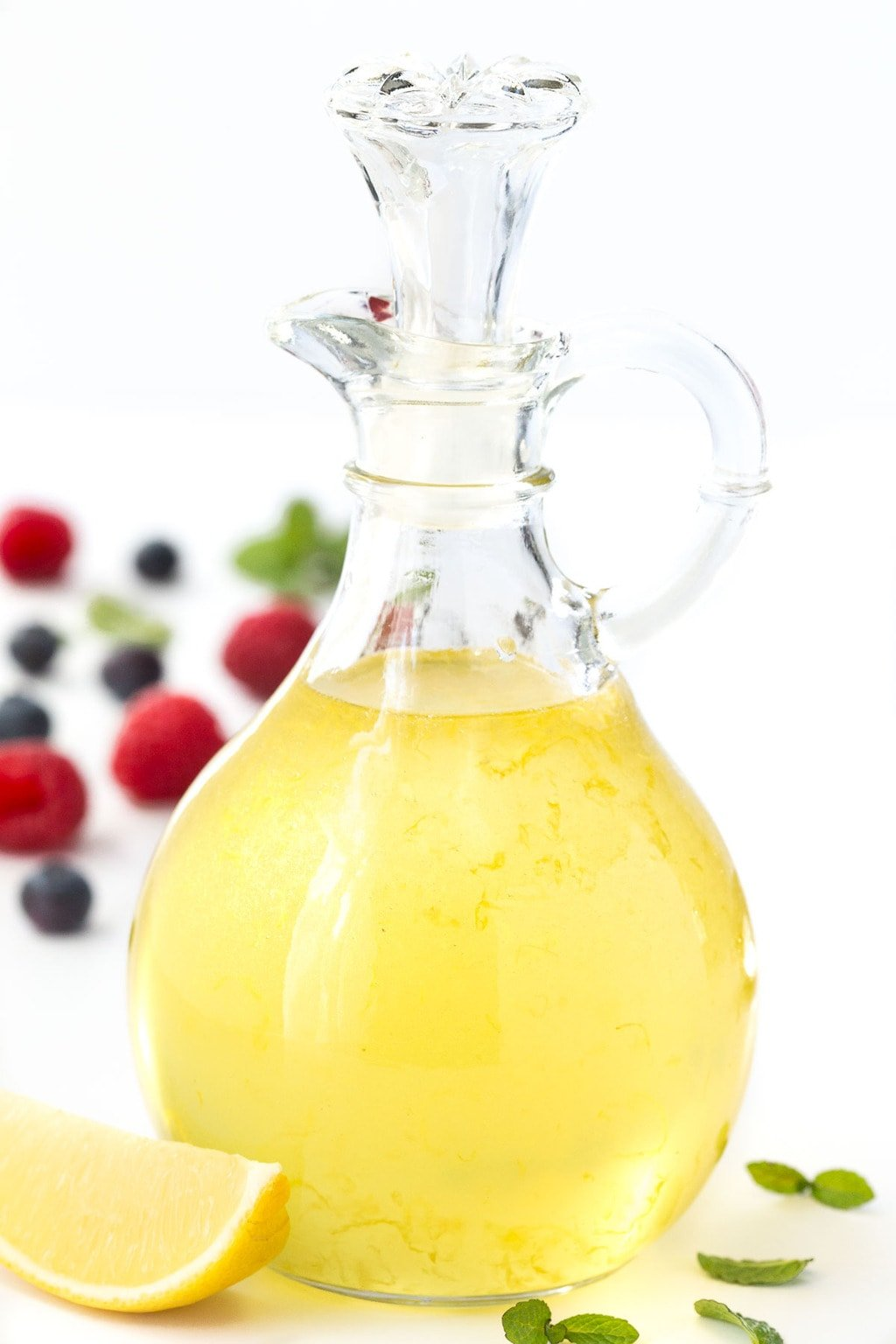 A photo of a glass pitcher of Limoncello Syrup with fruit in the background.