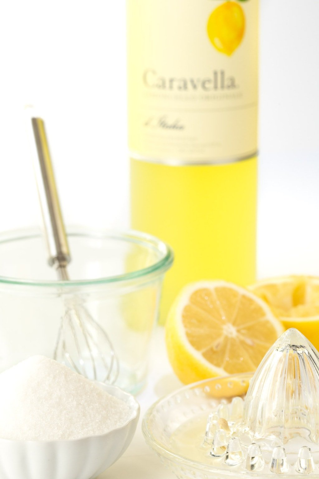 Photo of the ingredients and equipment for making Limoncello Syrup and Dessert Sauce with a bottle of Caravella lemon liquor in the background.