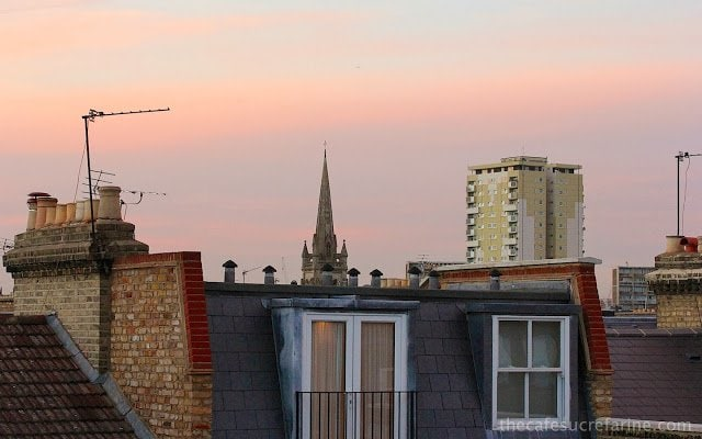 Rooftop view of the tops of houses, churches and buildings at sunset in London, England.