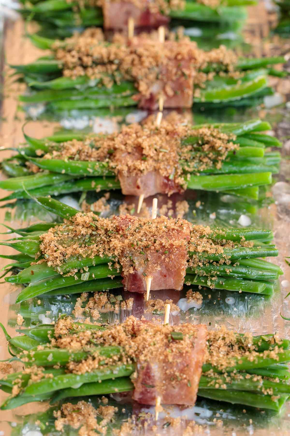 Closeup photo of a row of Make-Ahead Bacon Wrapped Green Beans before going into the oven.