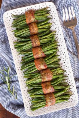 Overhead vertical photo of Bacon Wrapped Green beans on a white lattice serving platter.