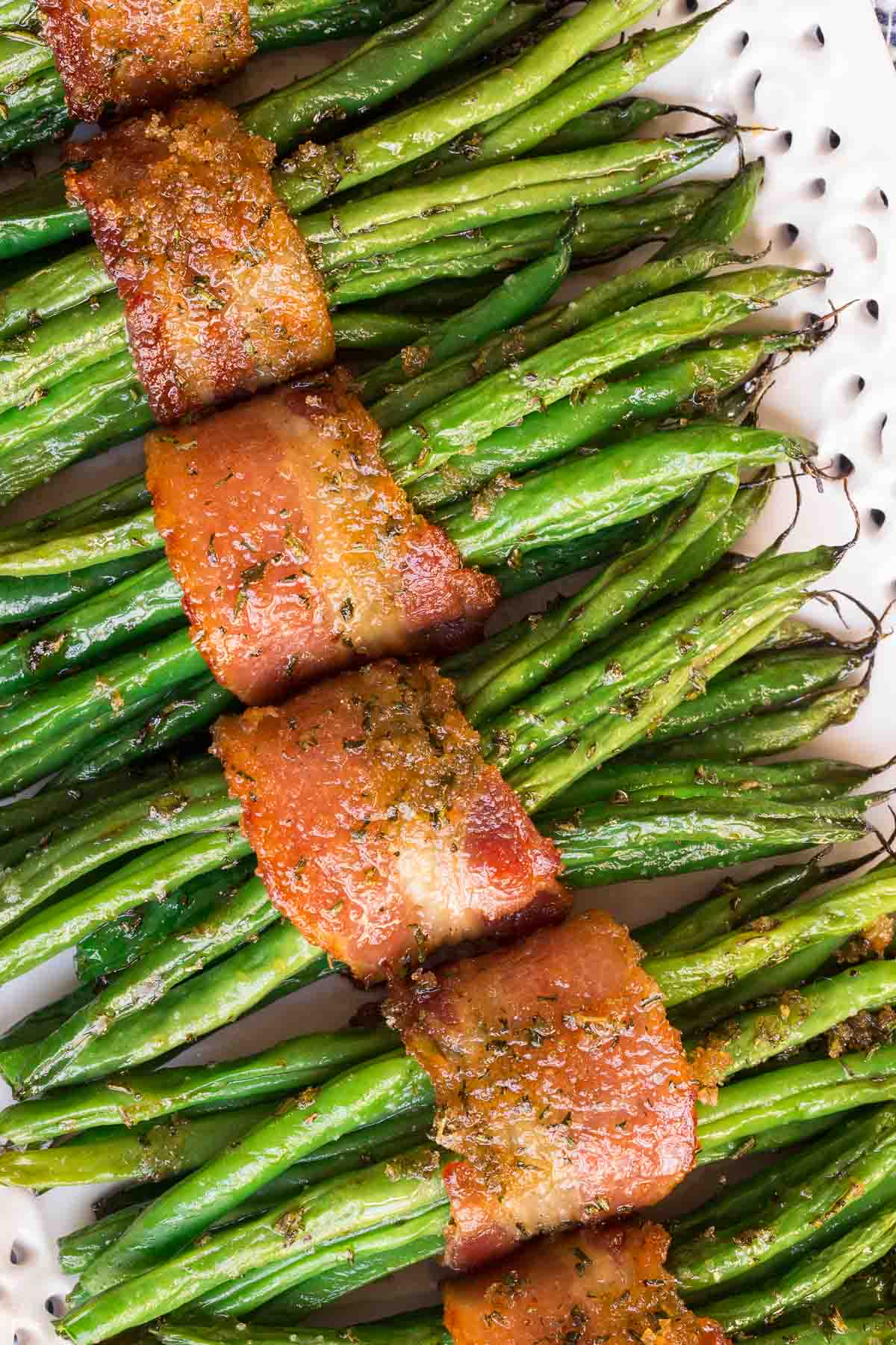 Ultra closeup photo of Make-Ahead Bacon Wrapped Green Beans on a white lace patterned serving platter.