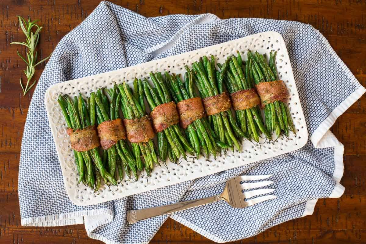 Overhead photo of a presentation platter of Make-Ahead Bacon Wrapped Green Beans on a blue and white towel.