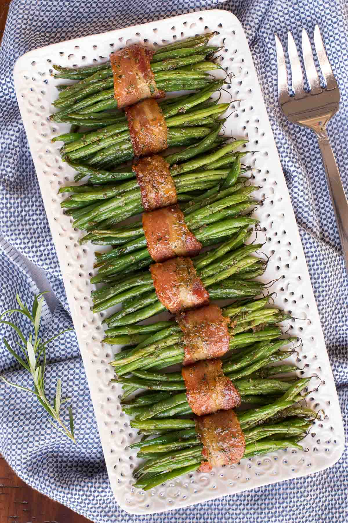 Overhead closeup photo of Make-Ahead Bacon Wrapped Green Beans on a white serving platter on a blue and white towel.