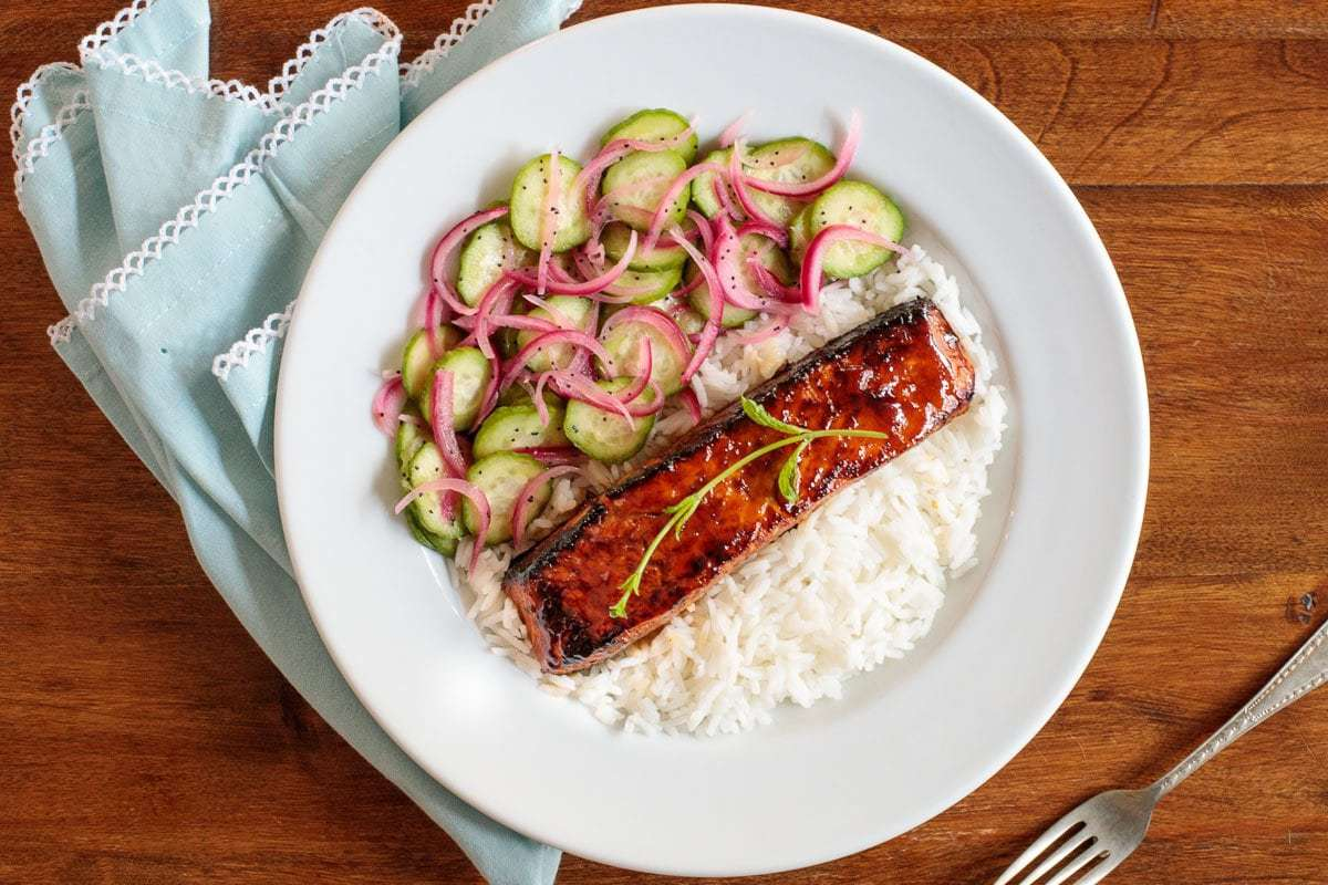 Overhead horizontal photo of a white plate with Make-Ahead Honey Coriander Salmon with red onions and cucumbers laying on a bed of white rice.