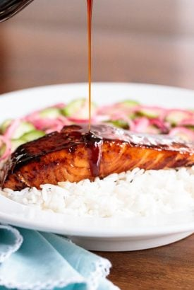 Vertical closeup photo of Make Ahead Honey Coriander Salmon on a bed of rice with sauce being poured over it.