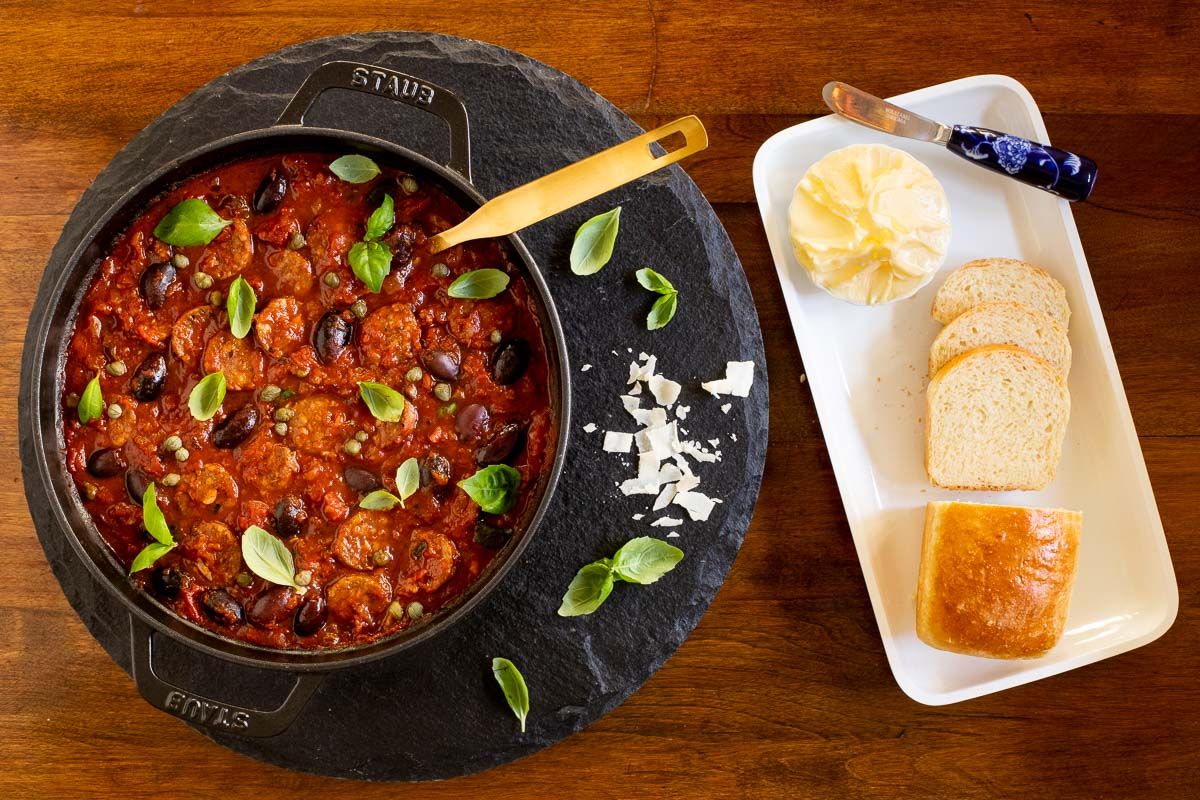 Overhead vertical photo of a pot of Italian Sausage Puttanesca on a round slate surface with fresh homemade brioche bread and butter.