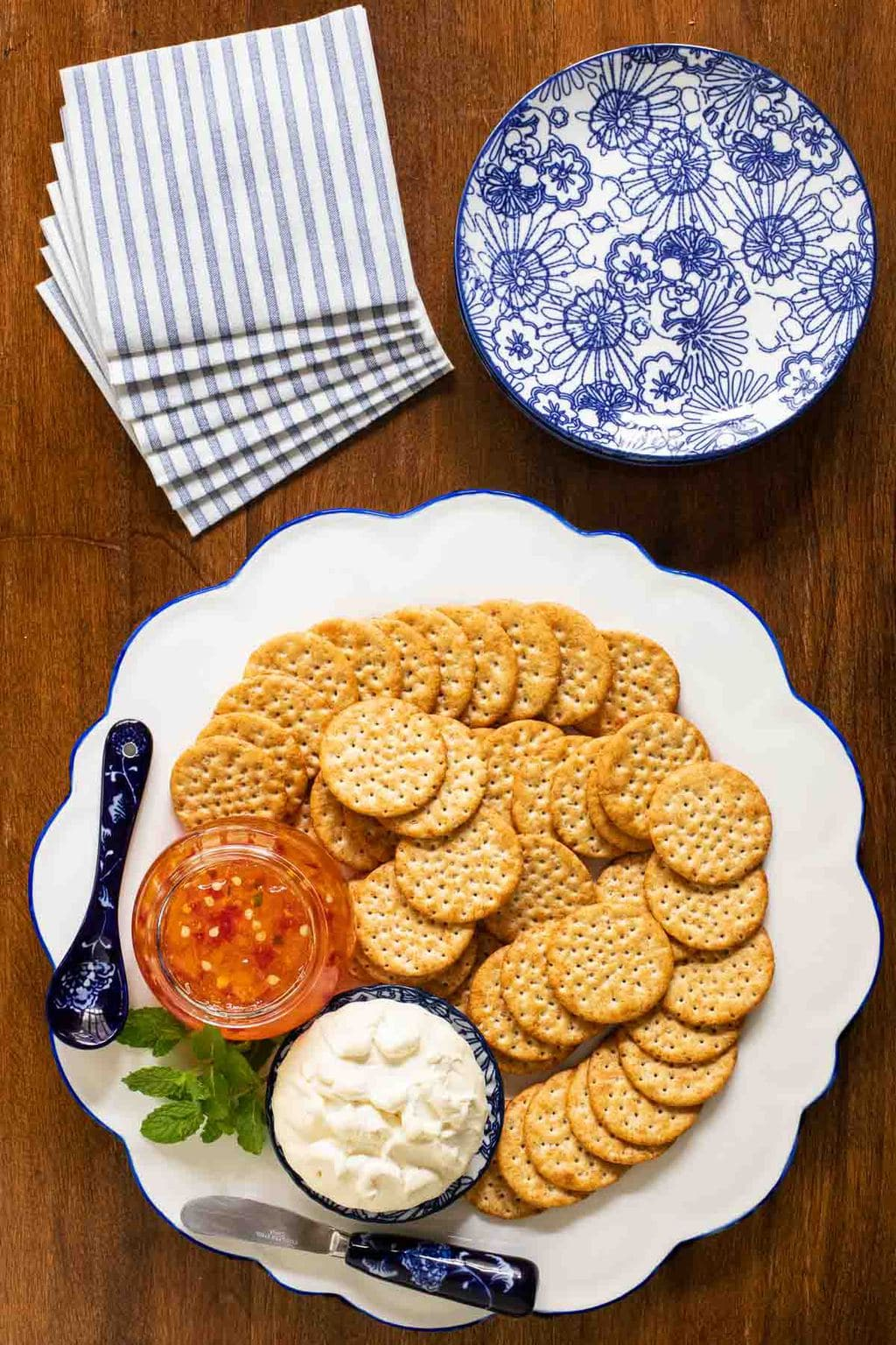 Overhead photo of an appetizer plate filled with crackers and featuring a jar of Mango Jalapeño Pepper Jelly.