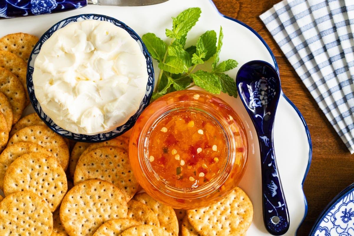 Overhead vertical closeup of an appetizer tray featuring Mango Jalapeño Pepper Jelly.