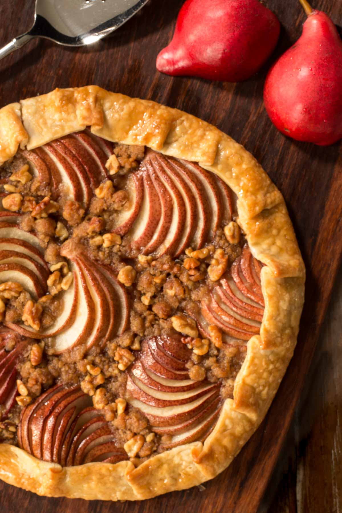 Overhead vertical photo of a Maple-Glazed Red Pear Galette on a wooden cutting board.