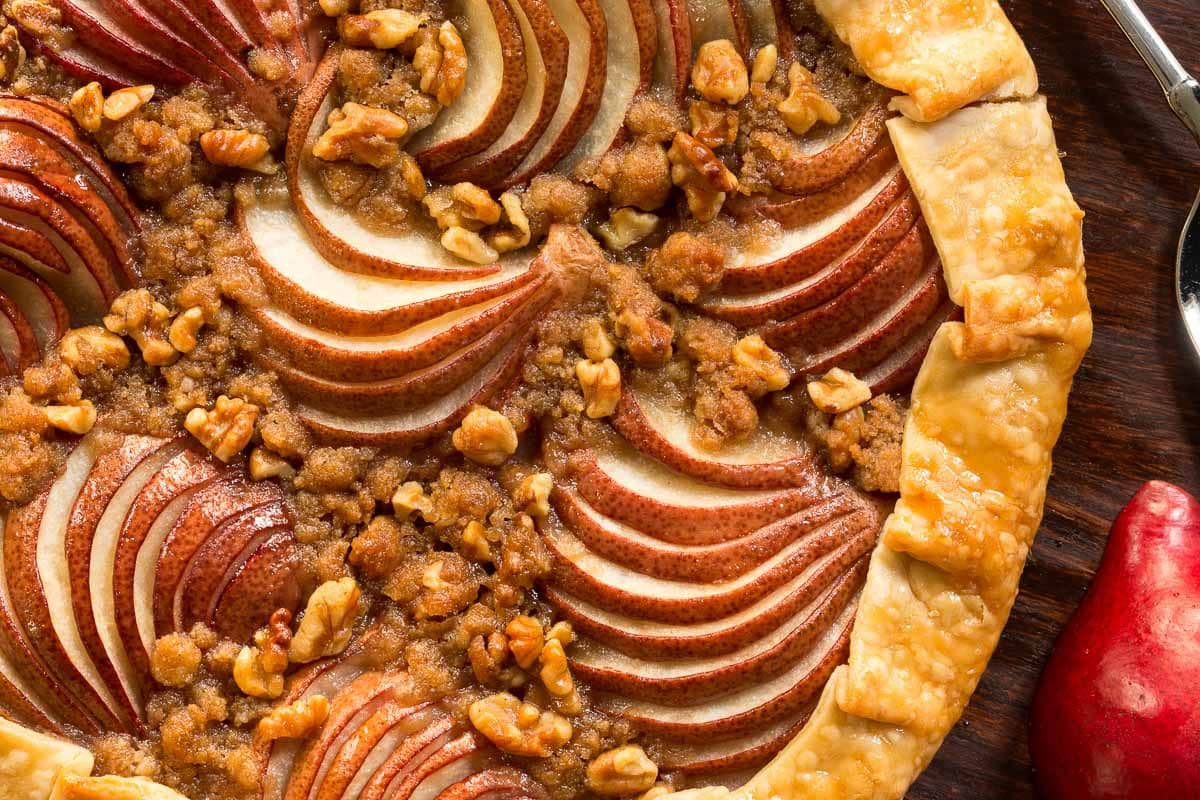 Overhead photo of a Maple-Glazed Red Pear Galette on a wood table.