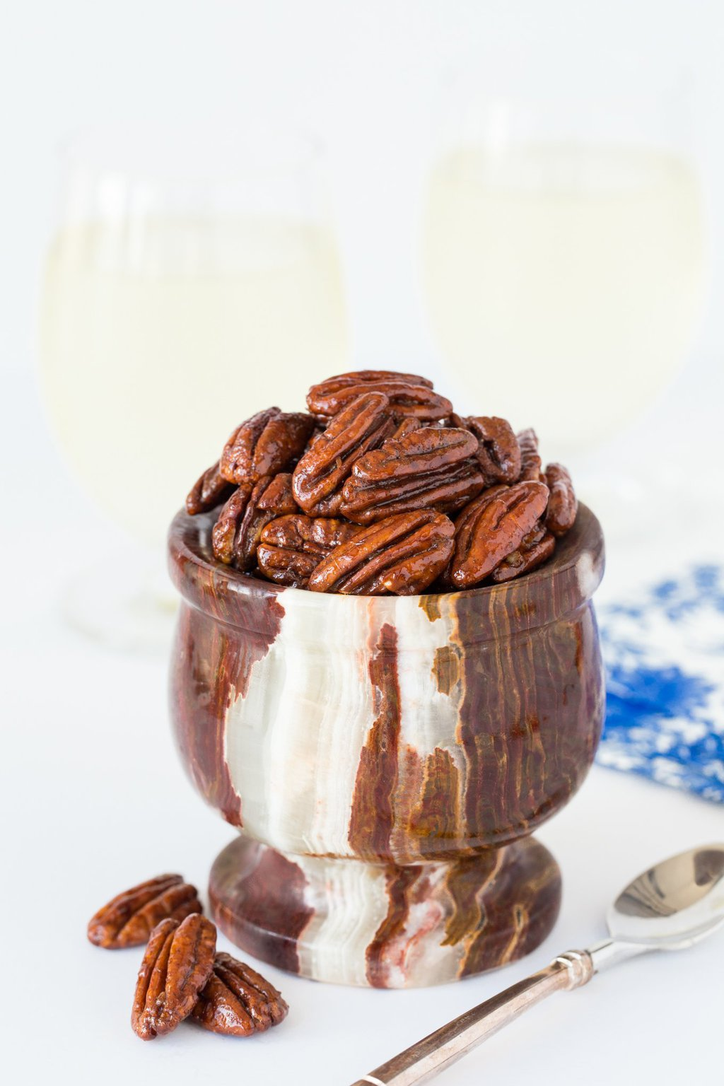 Vertical picture of Maple Molasses Glazed Pecans in a small stone bowl on a white background