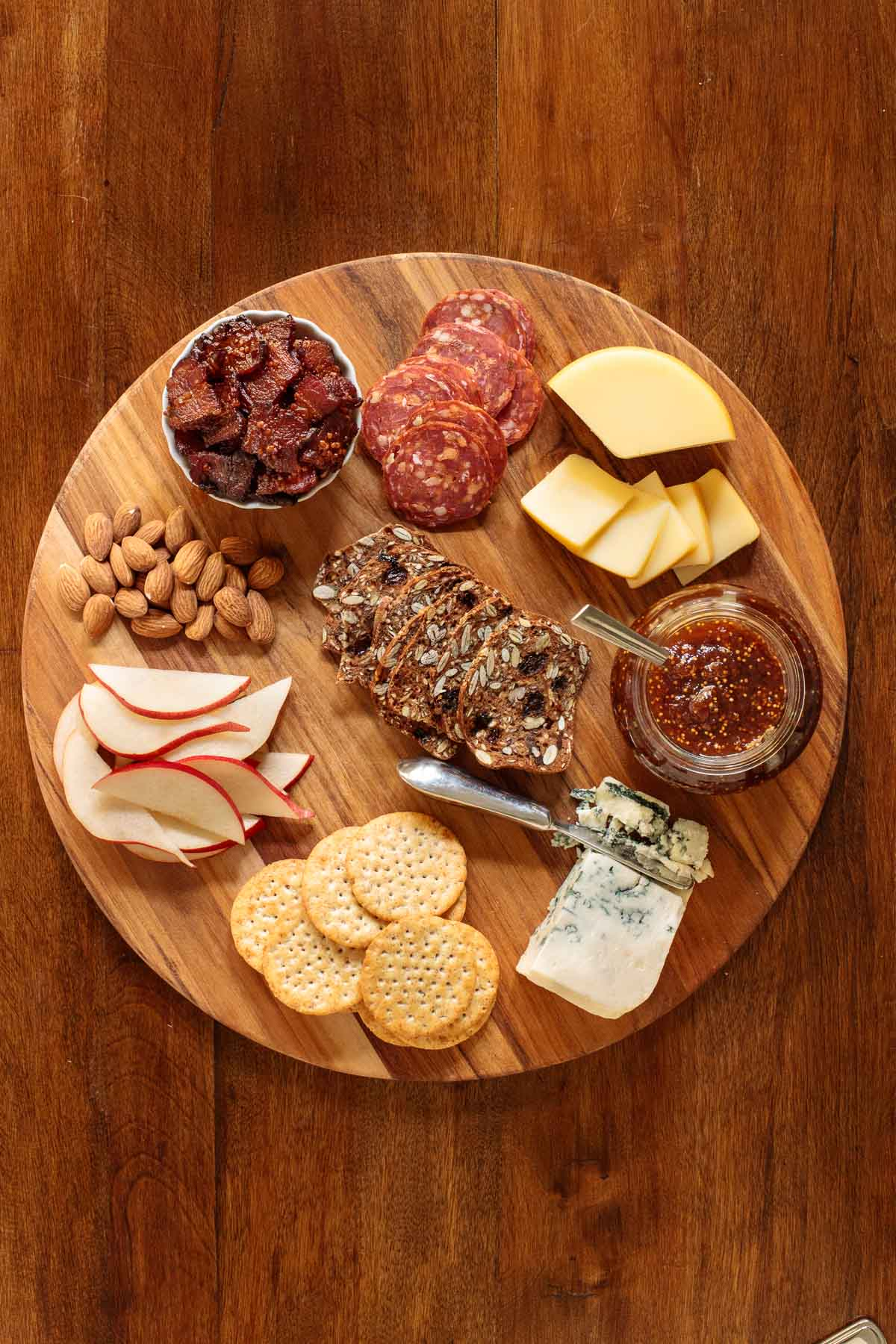 Overhead photo of a cheese tray featuring Maple Mustard Candied Bacon along with various cheeses, crackers, almonds, sliced apples and fig jam.